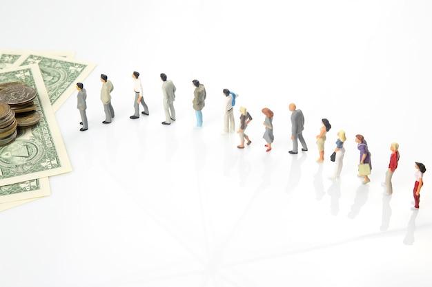 Gente en miniatura. diferentes personas hacen fila una tras otra para recibir dinero.