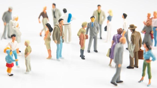 Gente en miniatura. diferentes personas se paran sobre un fondo blanco. comunicación de la sociedad de diferentes generaciones