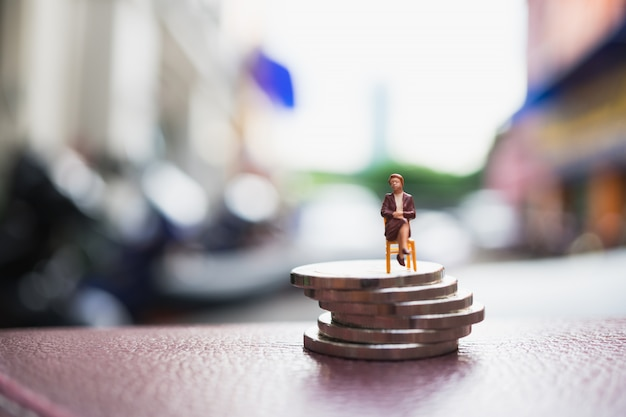 Gente miniatura, empresaria sentado en la pila de monedas