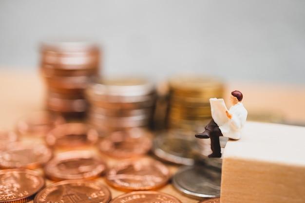 Gente miniatura, empresario leyendo periódico en monedas de pila
