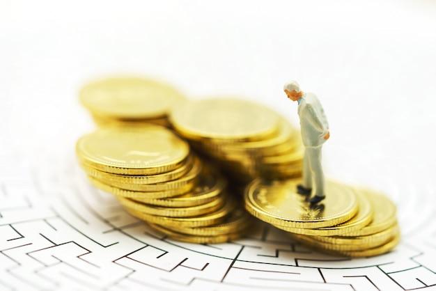 Gente en miniatura: empresario de pie en el centro del laberinto con la pila de monedas.