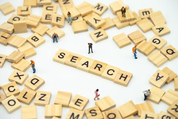 Gente en miniatura de empresarios de pie con la palabra madera buscar encontrar algo