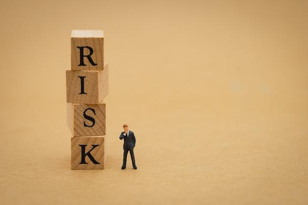 Gente en miniatura empresarios de pie con la palabra madera riesgo
