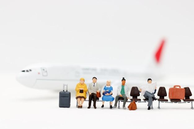 Gente miniatura con equipaje esperando avión. conceptos de transporte.