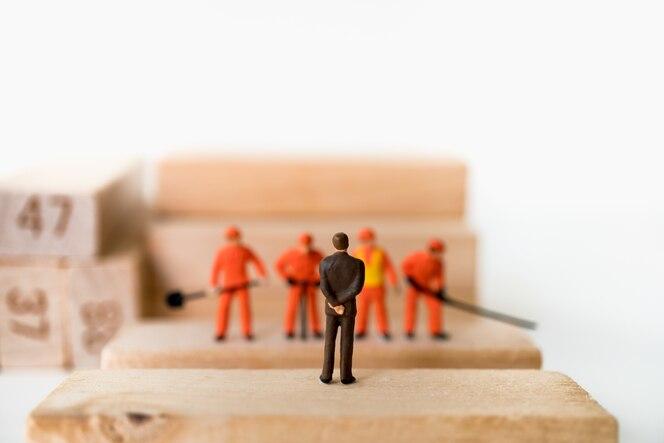 Gente miniatura, equipo del jefe e ingeniero que se coloca en bloque de madera