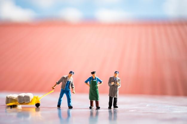 Gente miniatura, equipo de logística en el sitio de trabajo, utilizando para el concepto de logística y de negocios