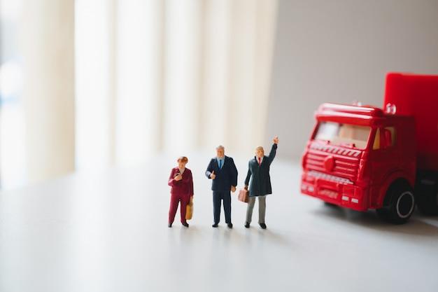 Gente en miniatura, equipo de negocios de pie con contenedor de camión rojo