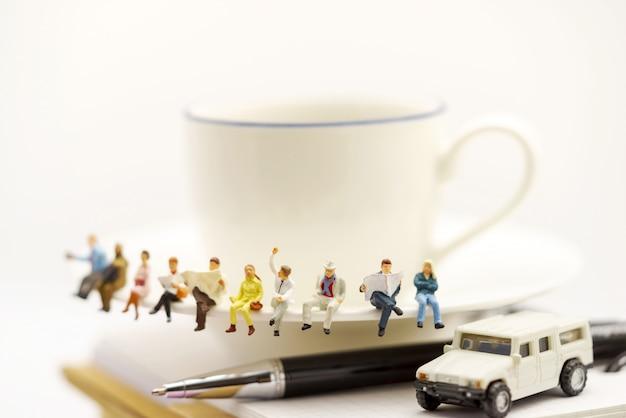 Gente en miniatura: equipo de negocios sentado en una taza de café con noticias de la mañana.
