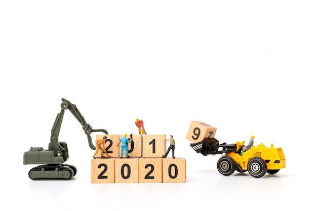 Gente en miniatura: el equipo de trabajadores crea el bloque de madera número 2020
