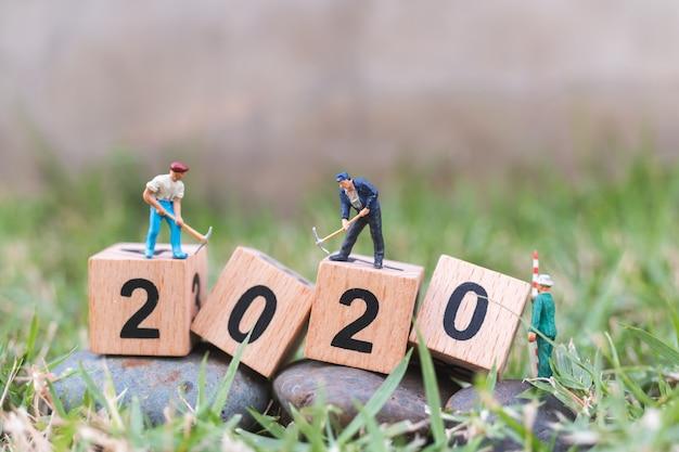 Gente en miniatura, equipo de trabajadores crean bloque de madera número 2020