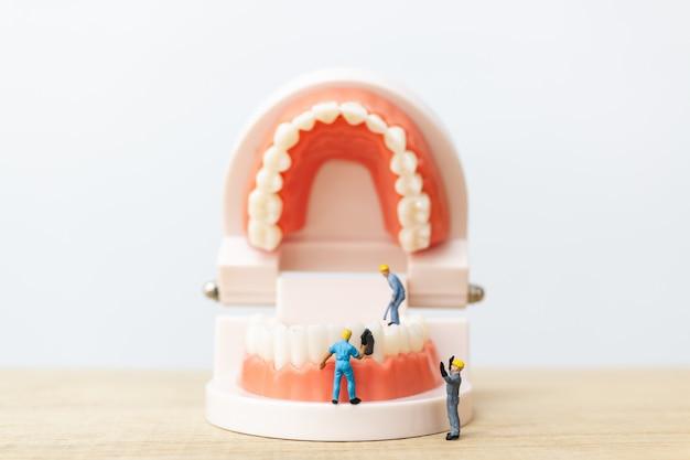 Gente en miniatura: equipo de trabajadores reparando un diente