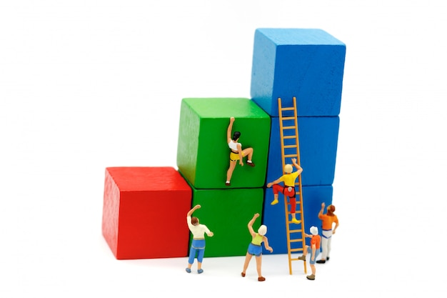 Gente en miniatura: escalador mirando hacia arriba mientras desafía la ruta en el gráfico de crecimiento con escalera de madera.