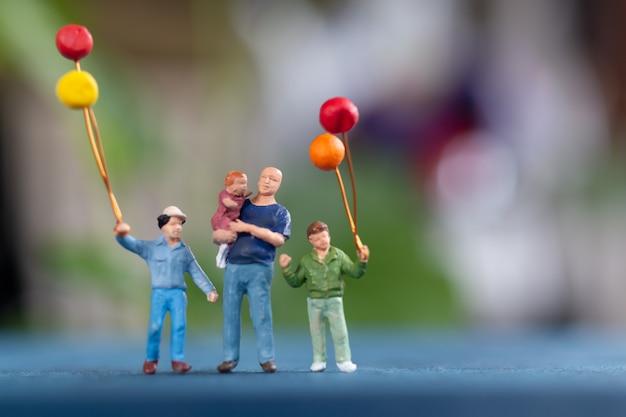 Gente en miniatura: familia feliz con globo en el parque