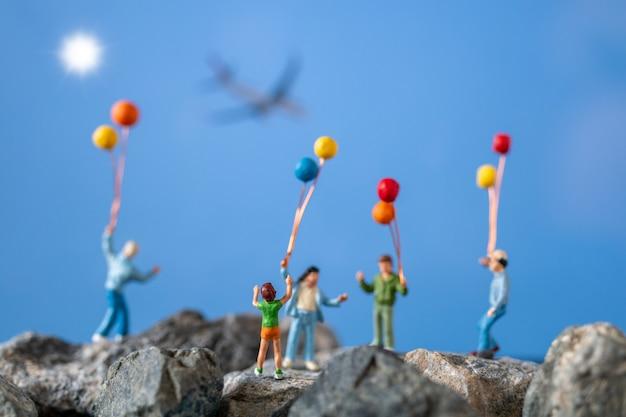 Gente miniatura, familia feliz que sostiene el globo en la roca con el cielo azul