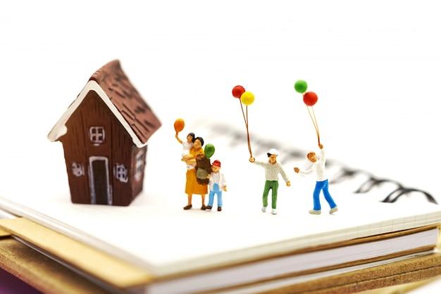 Gente en miniatura: familia y niños disfrutan con globos de colores y casa.