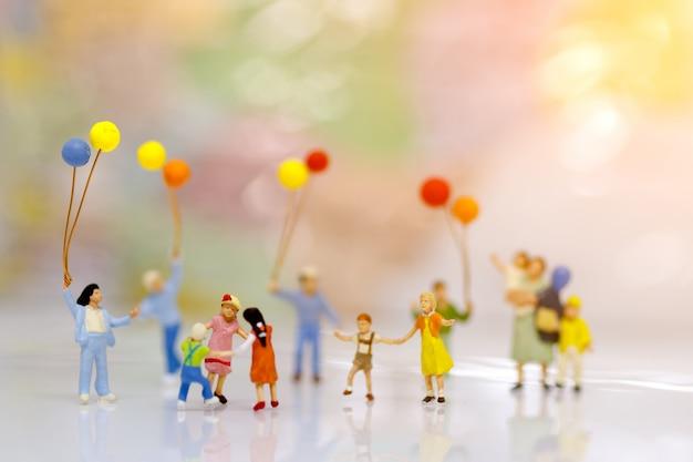 Gente miniatura, familia y niños con globos de colores, concepto de familia.