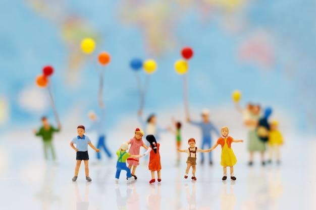 Gente miniatura, familia y niños con globos de colores de pie delante de la casa.
