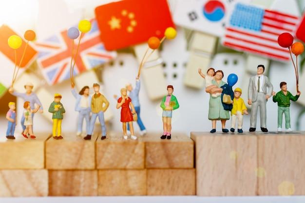 Gente miniatura, familia y niños con globos de colores de pie sobre un bloque de madera.