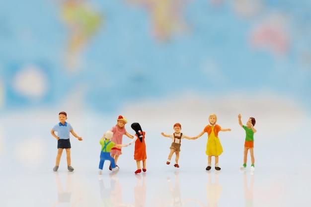 Gente miniatura, familia y niños con globos de colores.