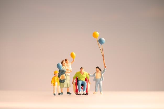 Gente en miniatura familia positiva cuidando a su padre discapacitado