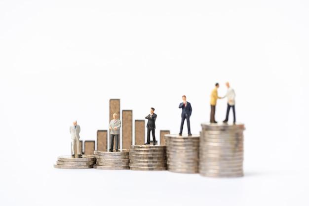 Gente en miniatura: grupo de empresario de pie en la pila de monedas con el letrero de madera del gráfico de barras como telón de fondo