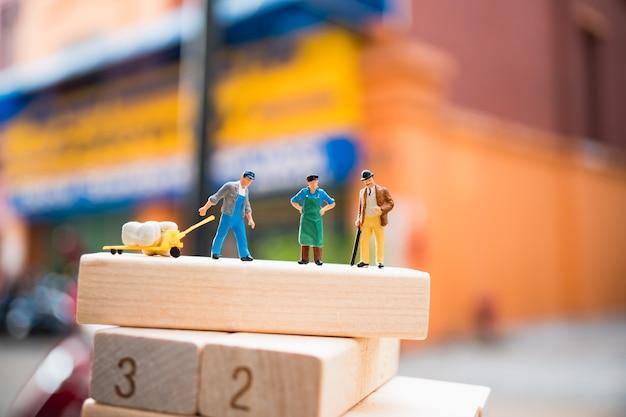 Gente miniatura, grupo de hombre de pie en el sitio de trabajo, utilizando para el concepto de logística y de negocios