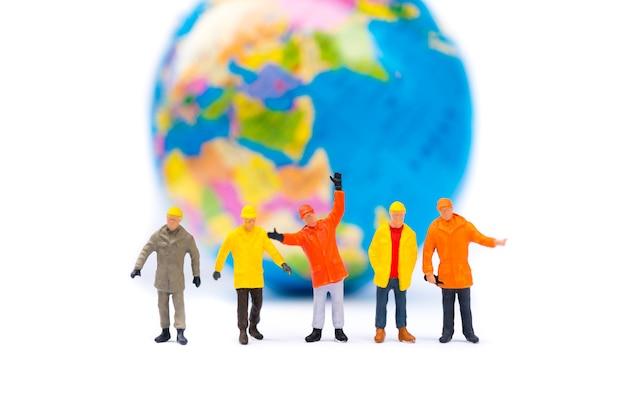 Gente miniatura, grupo de trabajadores que se colocan en fondo del mini planeta