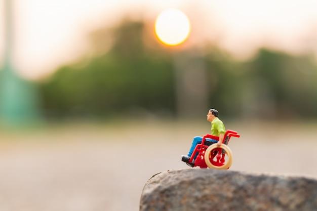 Gente en miniatura: hombre discapacitado sentado en silla de ruedas.