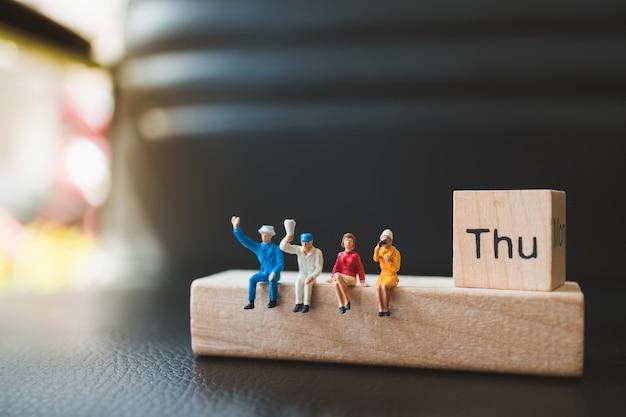 Gente miniatura, hombre y mujer que se sientan con el bloque de madera de jueves usando como concepto del negocio