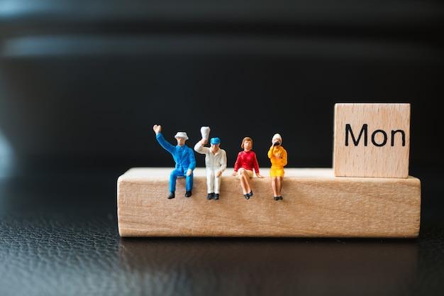 Gente miniatura, hombre y mujer que se sientan con el bloque de madera de lunes usando como concepto del negocio