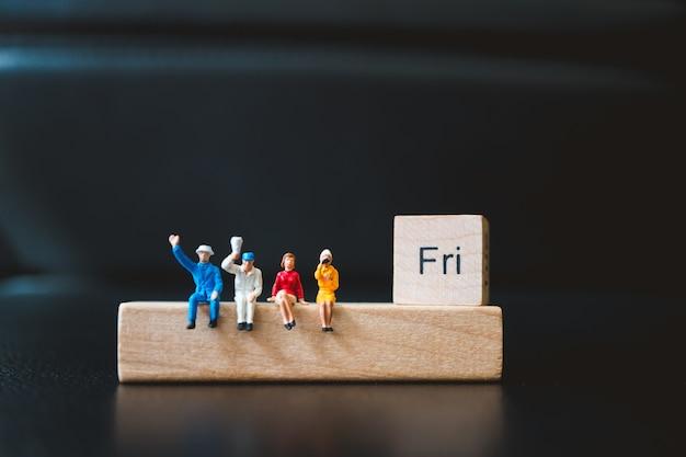 Gente miniatura, hombre y mujer que se sientan con el bloque de madera del viernes usando como concepto del negocio