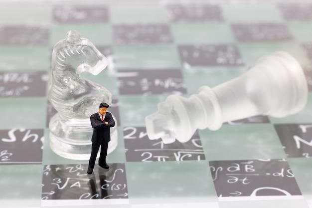 Gente en miniatura, hombre de negocios con pie de ajedrez de cristal en el tablero de ajedrez.