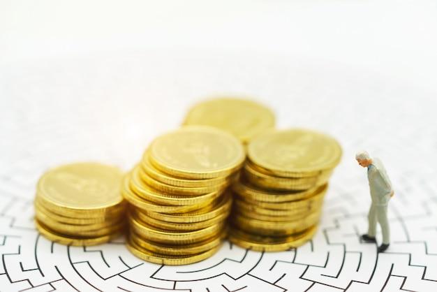 Gente en miniatura, hombre de negocios de pie en el centro del laberinto con pila de monedas