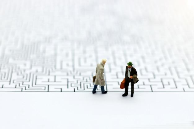 Gente miniatura: hombre de negocios de pie en el inicio del laberinto.