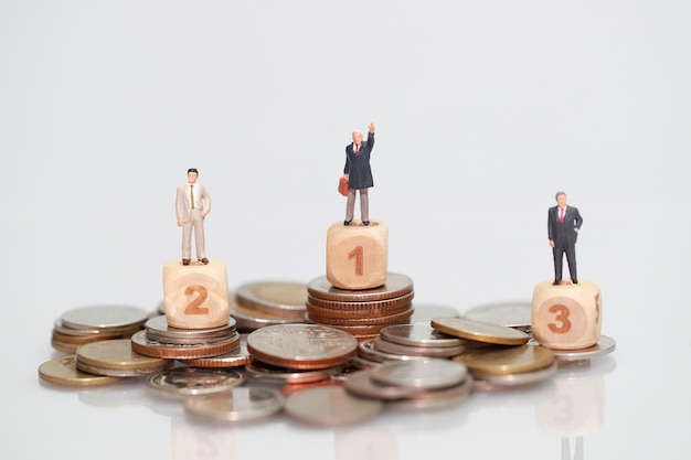 Gente en miniatura: hombre de negocios de pie en monedas de apilamiento