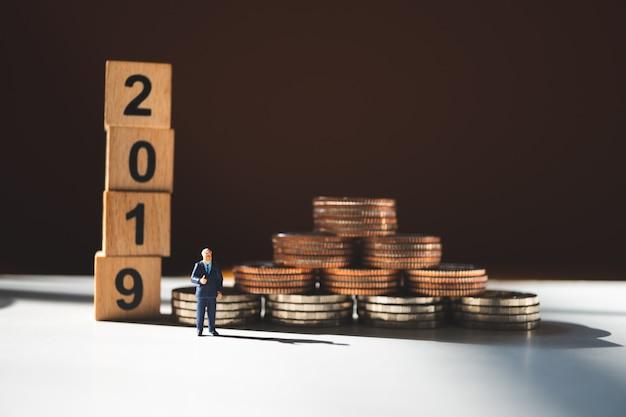 Gente en miniatura, hombre de negocios de pie con monedas de pila y año 2019.