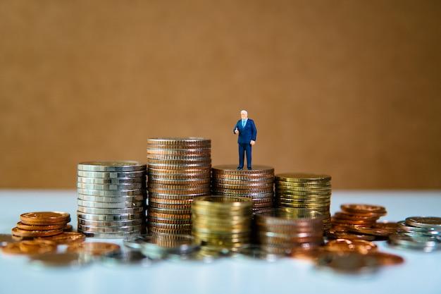 Gente miniatura, hombre de negocios de pie sobre un montón de monedas