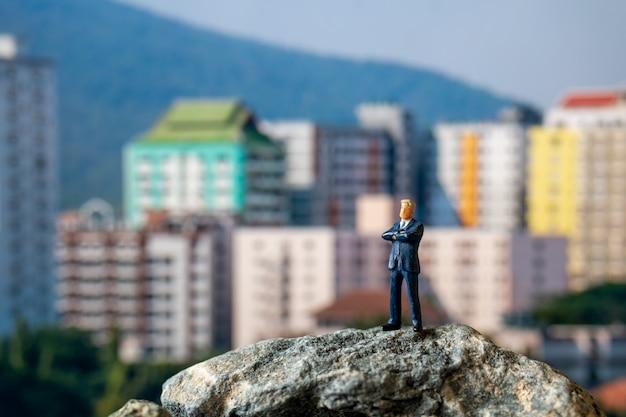 Gente en miniatura, hombre de negocios de pie sobre la roca con el edificio