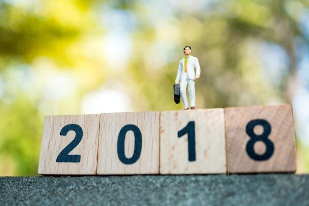 Gente miniatura, hombre de negocios que se coloca en bloque de madera del año 2018 usando como negocio, financiero y le
