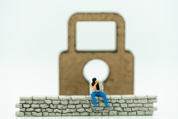 Gente miniatura: hombre de negocios sentado en la pared con llave maestra.