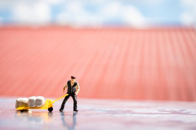 Gente miniatura, hombre que transporta carga en el sitio de trabajo, utilizando para el concepto de logística y de negocios
