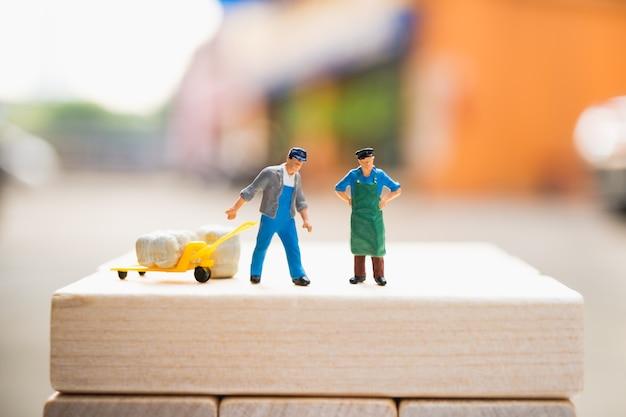 Gente miniatura, hombre en el sitio de trabajo, utilizando para el concepto de logística y de negocios