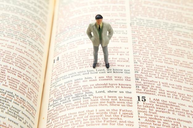 Gente en miniatura. el hombre se para en el texto de la biblia. busca el camino de la vida. yo soy el camino.