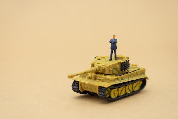 Gente en miniatura, hombres de negocios de pie con un modelo de tanque en la parte posterior. negociación