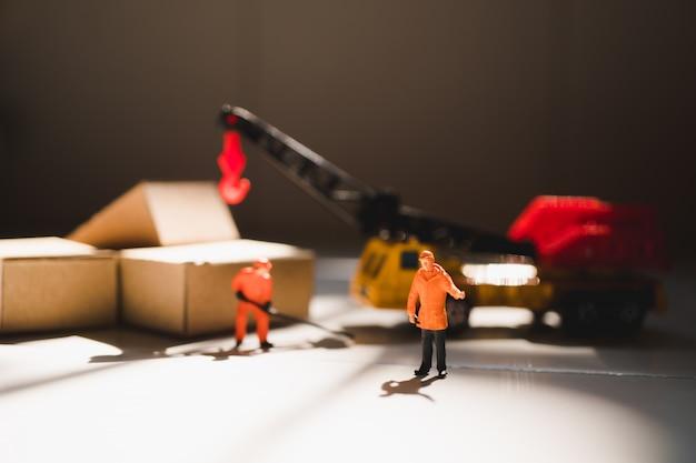 Gente en miniatura, ingeniero trabajando en la obra.
