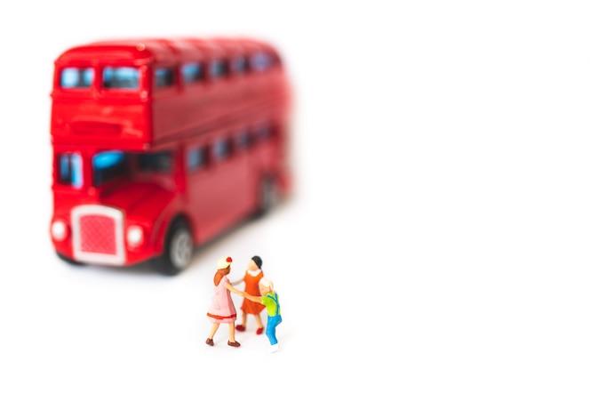 Gente miniatura, los niños van a la escuela aislada en el fondo blanco
