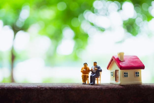 Gente miniatura, marido y mujer relajarse en el fondo de naturaleza verde