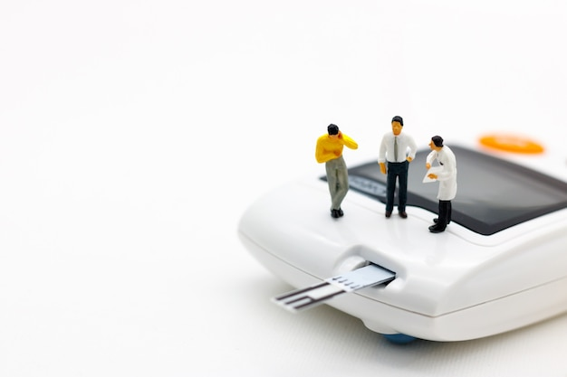 Gente en miniatura: médicos de pie con medidor de glucosa de diabetes y aguja de inyección.