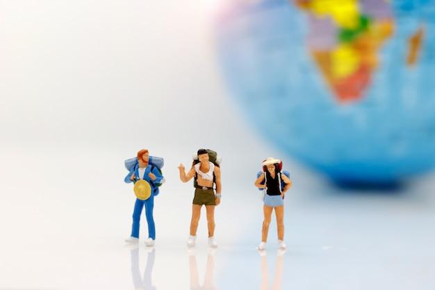 Gente en miniatura, mochileros con globo caminando hacia el destino.