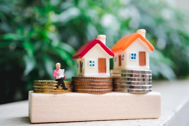 Gente miniatura, mujer leyendo en monedas de pila con casa colorida